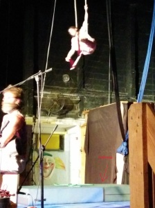 A girl is doing trapeze with a mattress below